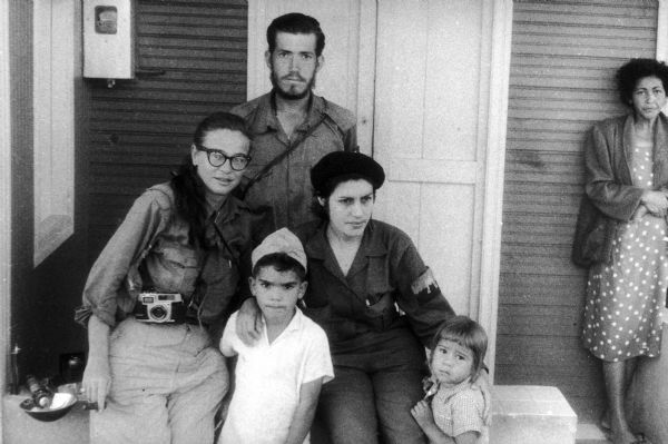 1958: Dickey Chapelle poses with Vilma Espin, who married Fidel Castro's brother Raul Castro. Also shown are two children (Espin and Castro's children?), and an older woman, who stands off to the side in the back. | Wisconsin Historical Society