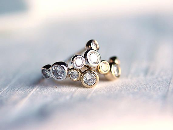 Don't let anyone burst your bubble! Show off these sassy stackable bubble rings in a smart blazer or cocktail dress. These versatile rings will command attention and feature white round-cut CZ stones, an adjustable band and come in your choice of a high polished gold or silver plated finish. Mix two finishes to follow the latest metallic silver & gold trends. Light up the room with these stylish rings and you'll feel like you are floating!  -GOLD Crystals Open Ring Base material : Brass S...