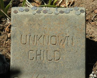 unknown child grave marker, anyone know what the coins on top of the stone are about?