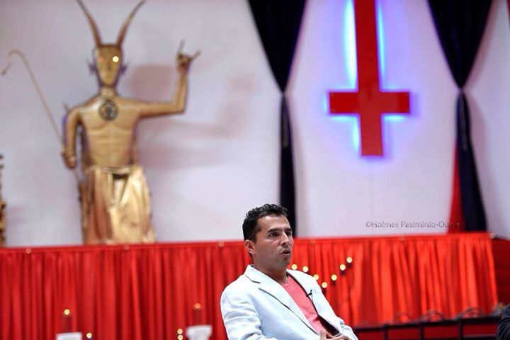 "Pastor at the satanic church in Colombia. Notice devil horns the satanic statue throws up. Not a coincidence that countless celebrities,politicians, royals, catholic popes and fake pretender ""christian religious"" leaders use. Also notice the upside down cross in white/red. This is satanic - people fail to open  eyes to acknowledge that the Catholic church uses this as well as Lady Gaga.  Not a coincidence - catholic church lies w/  lame explanation that it represents St ..."