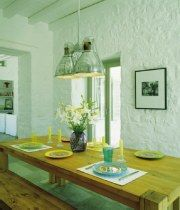 Στον ενιαίο χώρο της κουζίνας, προς την πλευρά της θάλασσας, τοποθετήθηκε ένα ξύλινο τραπέζι με παγκάκια primitive, inox λάμπες και ασπρόμαυρες φωτογραφίες με θέματα από την αγροτική ζωή.