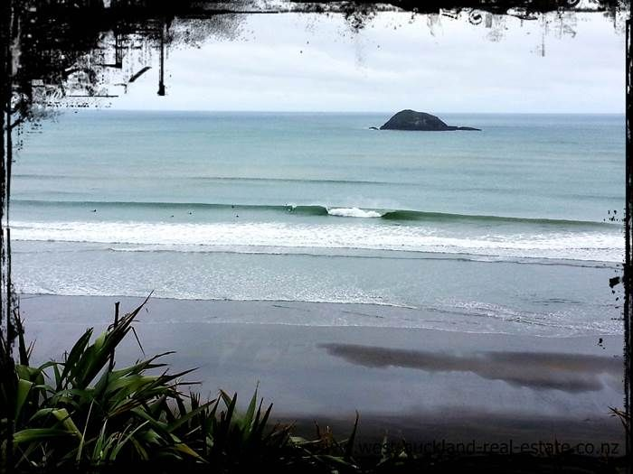 Surfer dropping in on a wave at Mud Bay Auckland