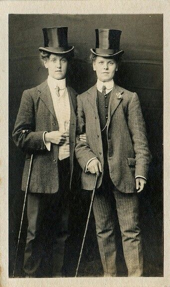 Two women in suits and top hats with canes.