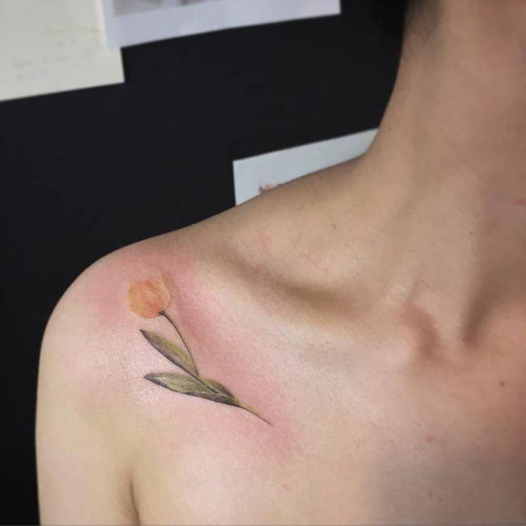 Yellow tulip tattoo on the shoulder. Tattoo artist: Muha Lee
