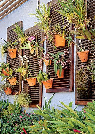 I adore the simplicity. It is beautiful and practical. If you like a lot of plants in your yard, the shutters would look great attached to a fence as well.