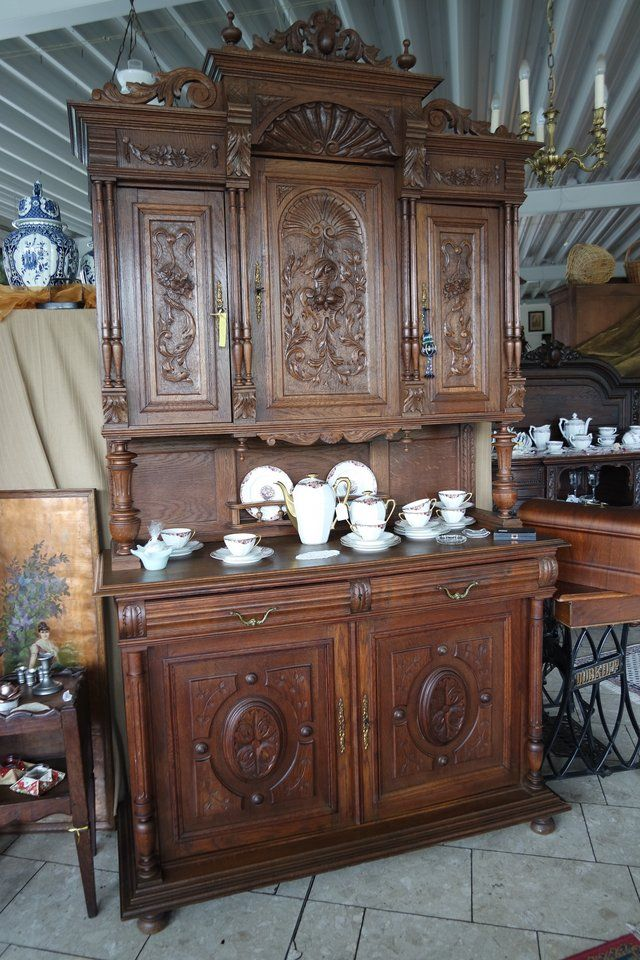This antique Henri II dining room hutch is made of tiger oak with rich wood  carvings