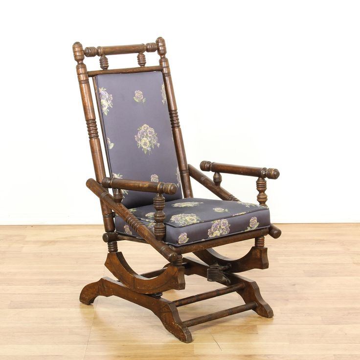 This victorian glider chair is featured in a solid wood with a glossy walnut finish. This rocking chair has carved spindle accents, a gliding seat base and purple upholstered seat cushions with floral pansy print. Eye catching accent chair perfect for decorating a room! #americantraditional #chairs #accentchair #sandiegovintage #vintagefurniture