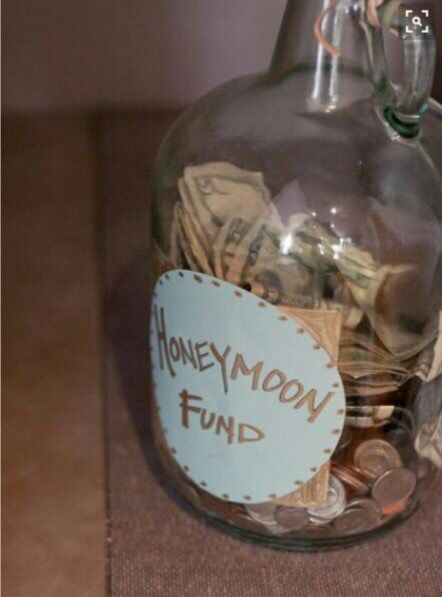 Jar for honeymoon fund sitting on the guestbook table