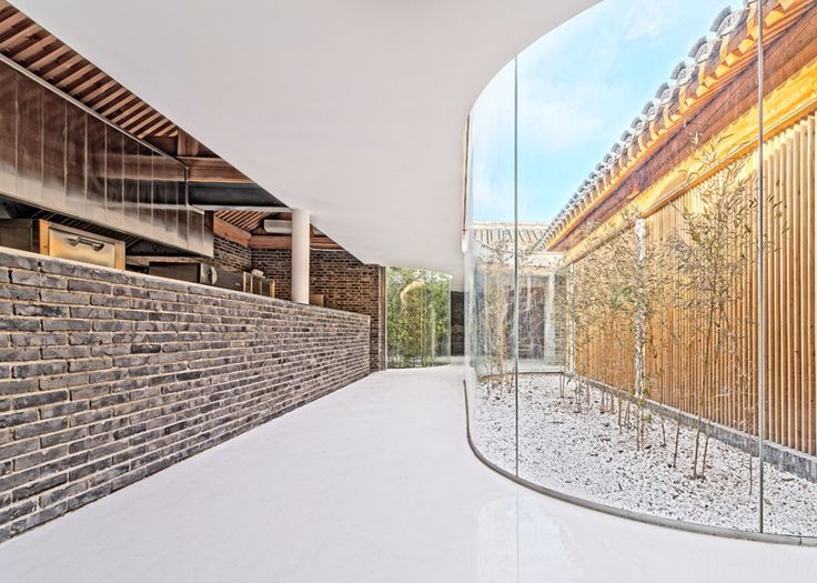 Curving glass walls enclose bamboo-planted courtyards in this tea house, which occupies a formerly derelict building complex in one Beijing's ancient neighbourhoods.