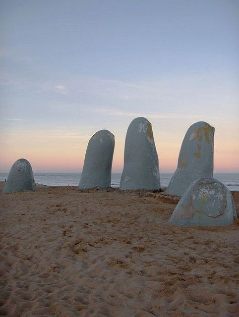 Mano de Punta del Este, a sculpture by Chilean artist Mario Irarrázabal depicts five human fingers emerging from sand. Brava Beach, Punta del Este, Uruguay.