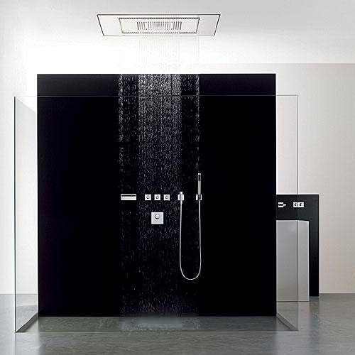 A sleek design bathroom with a sheer black shower wall where the water comes from the ceilling in sheets of rain. The symmetrical design is reminiscent of a Japanese Zen waterfall where minimalism and tranquility are central themes. The floor of cool grey marble provides a dramatic contrast for the pitch black backdrop created by the shower. #Shower #Black #Grey #White #Glass #Modern #Sleek #Design