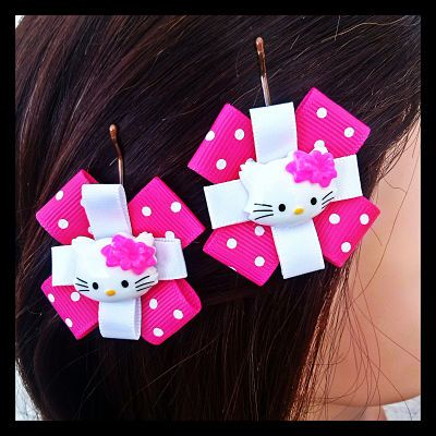 Pink polka dot and white ribbons adorned with a cat embellishment on bobby pins. Purrfect for those who love cats. These bobby pins feature a cheerfully cute cat fixed upon a white ribbon with a pink and white polka dot background ribbon. 6 Sets Available. $7.50 per set.