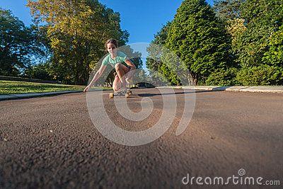Young girl skateboarding having fun on the tarred asphalt road driveway