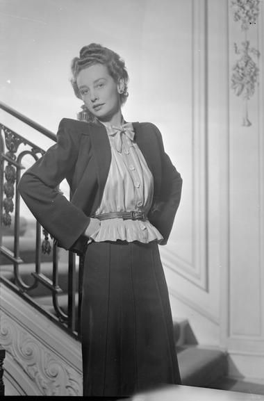 """Elspeth Champcommunal for Worth, 1945.  """"A model wears a navy blue spring suit by fashion designer Madame Champcommunal of Worth. The striped blouse is yellow and white, with a 'tucked basque', and is worn with a stitched belt. The blouse also has flower-shaped buttons and a bow at the neck.""""  LONDON FASHION DESIGNERS: THE WORK OF MEMBERS OF THE INCORPORATED SOCIETY OF LONDON FASHION DESIGNERS, LONDON, ENGLAND, UK, 1945  From the Imperial War Museum."""