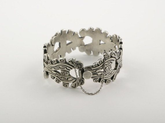 Wonderful Mid-Century J. Flores Taxco Sterling Silver Bracelet Circa 1940s, Signed by Artisan.  This chunky 6 panel link bracelet is the design of Mid Century Artisan, Jose Luis Flores of Taxco, Mexico. Each panel features full cutout work, a simple yet attractive motif and are all slightly curved and articulated, meaning the piece hugs the contour of the wrist beautifully. The chunky bracelet is assuredly weighty and secures with a tongue-in-groove box clasp and a 3 long safety chain.  Add…