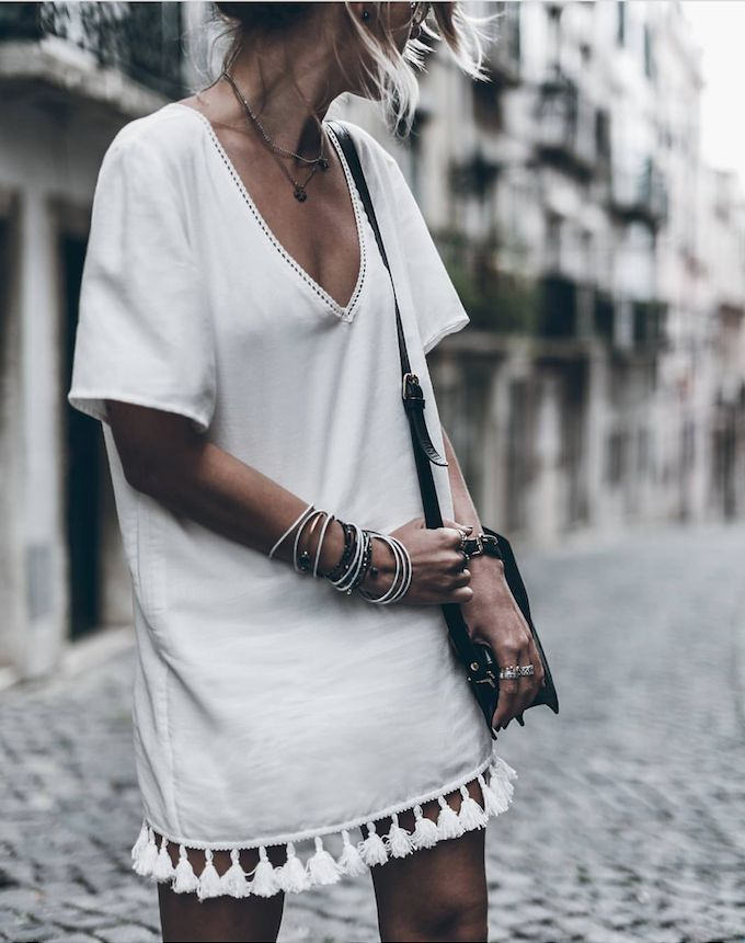 Invest in a subtle white dress with intricate embellishments, pairing the look with gold and silver bracelets, watches, and rings for effortless Summer style.
