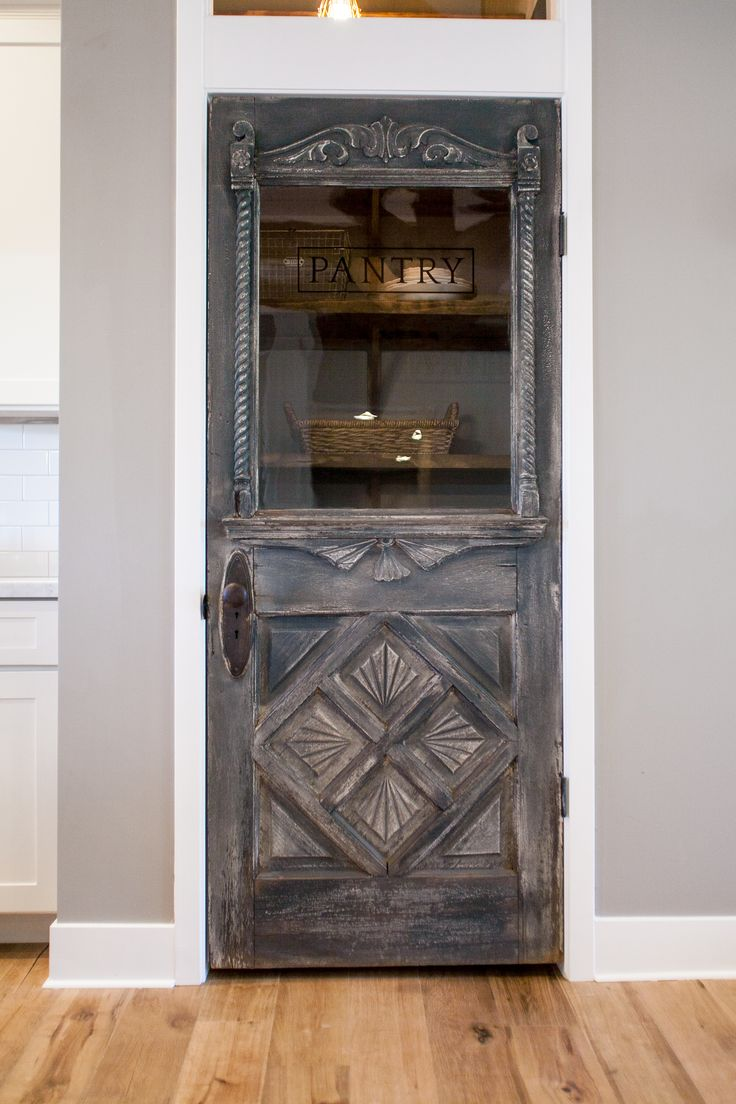 Antique farmhouse door repurposed as a pantry door by Rafterhouse