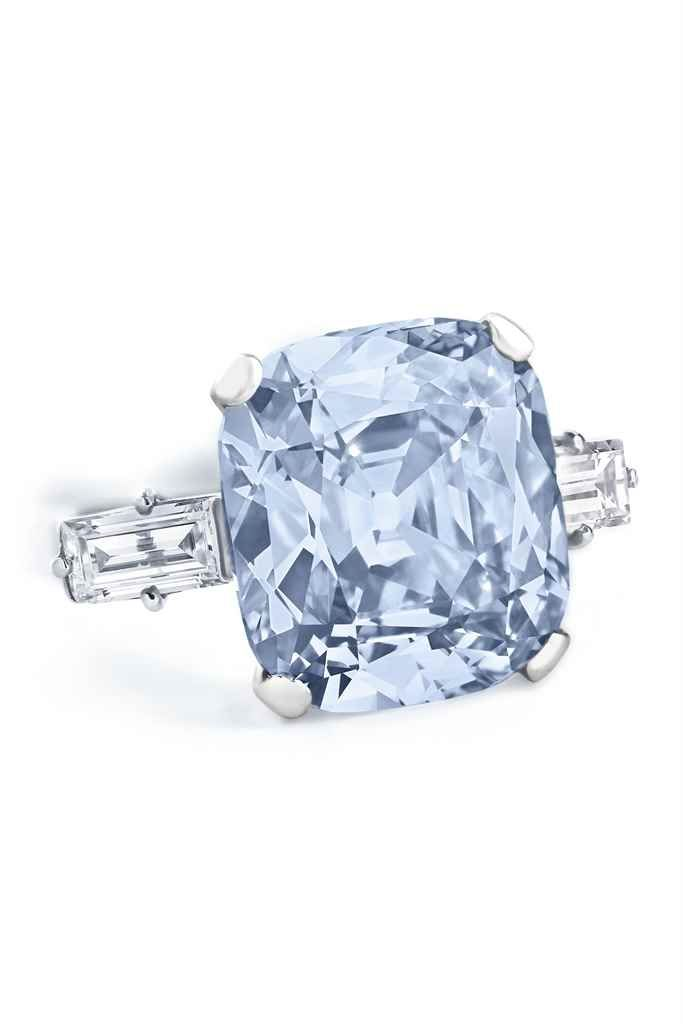A COLOURED DIAMOND RING. Set with a fancy intense blue cushion-shaped diamond, weighing approximately 7.97 carats, between baguette-cut diamond shoulders, ring size 6 ½, mounted in platinum. Accompanied by report no. 6187159503 dated 13 February 2017 from the GIA Gemological Institute of America stating that the diamond is Fancy Intense Blue colour, VS1 clarity.
