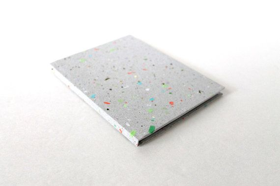 The cover of each of these little notebooks is wrapped with hand made paper, made in-house from recycled pieces of previous projects. The recycled paper is a pleasant neutral gray with various amounts and colors of paper flecks and the occasional plant material.