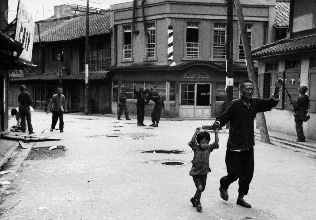 US soldiers stop and search residents of a South Korean city, looking for suspected Communist sympathizers. A man and young boy walk down the street with their hands in the air. 1950