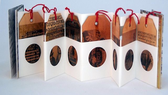 "Robyn Foster ""The Missing Typewriter Key""    Title no. #69. Edition no. 12/12. 11.7cm wide x 7.7cm tall x 2.7cm deep. Tabbed accordion book with fold-up pocket and inserts; black Canson paper box; 8 removabe tags with tabs and red string, shellaced; endpapers and postcards; typewritten and stencilled text."