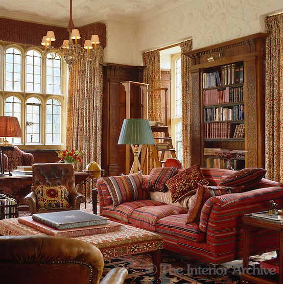 Robert Kime ~ The stuccoed library has carved wooden bookshelves and is decorated with an eclectic mix of fabric