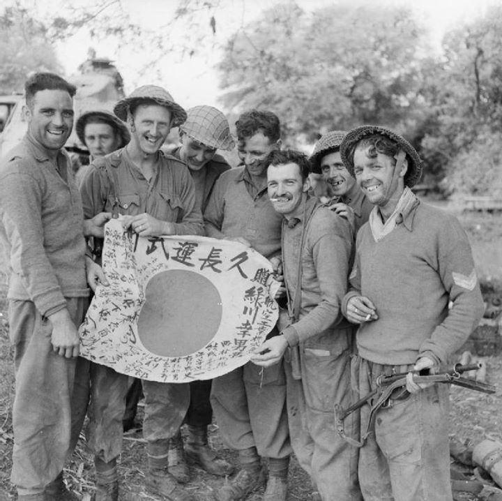 Men of the Royal Scots pose for a photograph with a Japanese flag taken as a souvenir after clearing the Japanese from Payan near Shwebo January 1945.