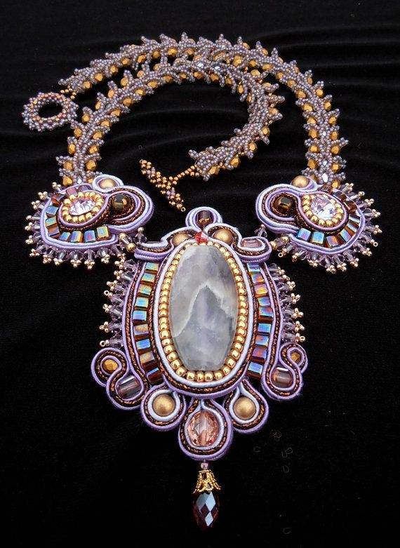 This necklace features a Amethyst cabochon center, wrapped in lilac, gold, bronze and purple so soutache. Embellished with lilac Swarovski crystals and mauve golden cube beads. Attached to a bead woven necklace made with matte gold Czech crystals and lilac seed beads. This necklace has a bead woven claps and measures around 18.5 inch.
