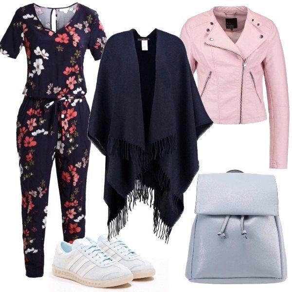 Jumpsuit blu a fiori, con manica corta e cinturino in vita, abbinata a sneakers color ghiaccio e zainetto azzurro. Giacca in fintapelle rosa e mantella blu. Look adatto a tutti i giorni, comoda ma trendy.