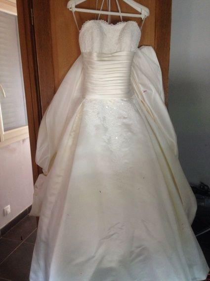 Robe de mariée de marque Pronovias taille 36, de couleur ivoire.  Robe en satin avec du drapée sur le ventre et un bustier brodé.  Très belle robe avec une traine de 5 mètres de long. La robe se ferme avec des petits boutons ivoire dans le dos et ils desc