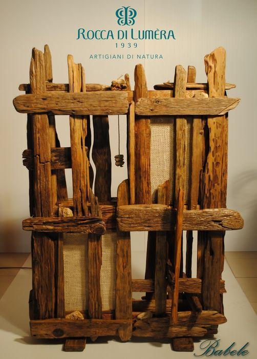 Babele-vloerlamp Rocca di Lumèra  Houten planken in diverse houtsoorten gedragen door de golven schijnbaar voorbereiden op het einde van hun levenscyclus totdat ze waren opgeslagen opgeruimd gepolijst en behandeld met natuurlijke wassen om ze te herstellen in hun oude glorie voor een lange tijd. Het werk naar boven schijnt en doet denken aan de buitenkant van een toren en net als de bijbelse toren van Babel heeft het binnen het elementen uit verschillende plaatsen verschillende talen spreken…