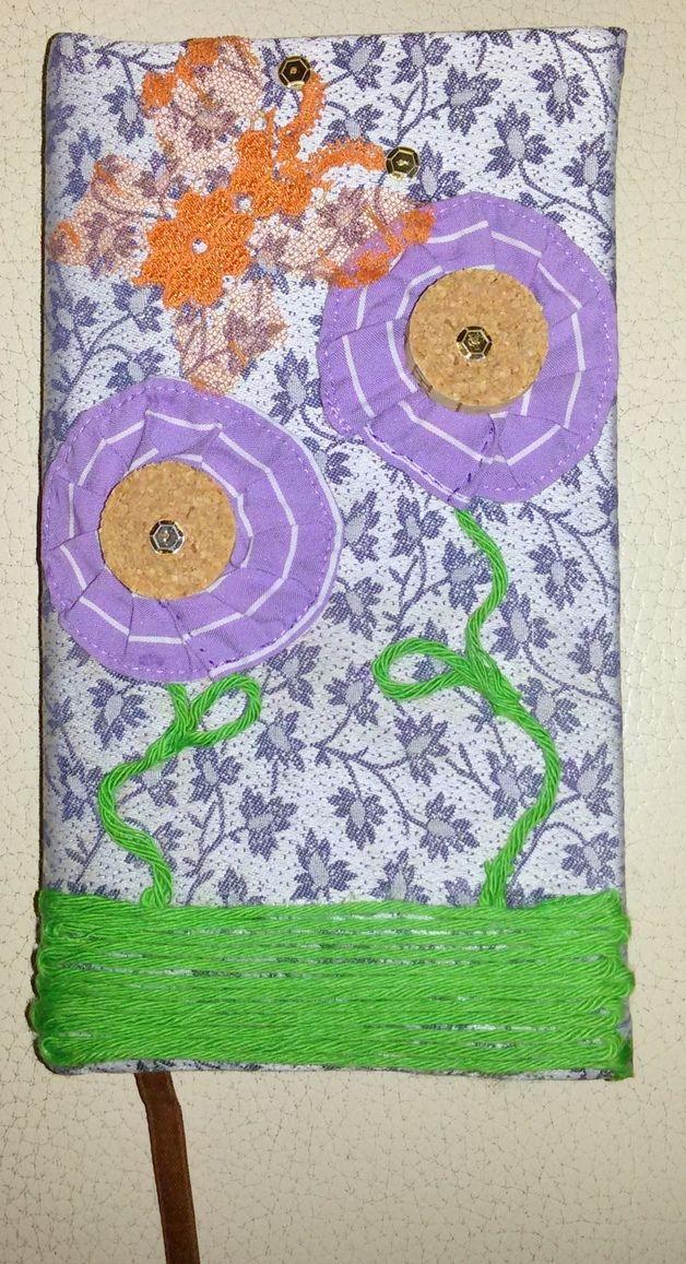 Agenda, notebook rivestita in stoffa di cotone celeste con motivo di foglie e decorata con due fiori realizzati con tappi di sughero, filo verde e stoffa di cotone lilla, e una farfalla di pizzo...