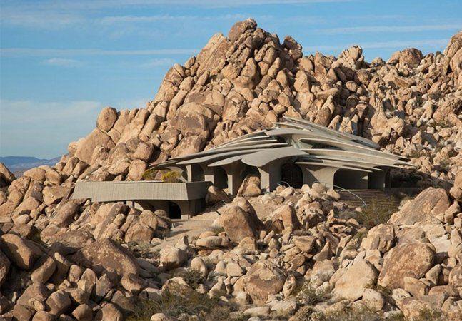 """Há quem diga que esta é uma casa de pedra, no melhor estilo Flintstones. Porém, basta um olhar mais demorado para entender a beleza de """"Organic Modern Estate"""", uma construção feita de cobre, aço e concreto que se confunde com as rochas do deserto do Parque Nacional de Joshua Tree, na Califórnia (EUA). A obra, idealizada pelo arquiteto Kendrick Bangs Kellogg em 1988, segue as linhas orgânicas das construções modernas. O telhado em forma de domo apresenta características irregulares que…"""