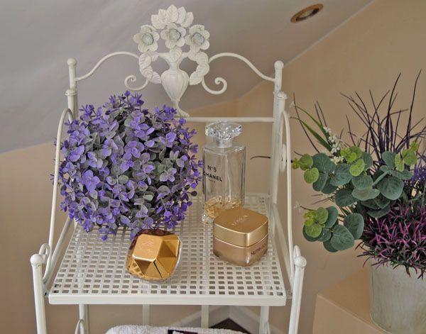 Wysoki , bardzo malowniczy, składany regał do łazienki w stylu prowansalskim. U góry piękny motyw zdobniczy stylizowanych kwiatów. Cztery półki dają dużą przestrzeń użytkową.Regał jest składany i łatwy do przenoszenia w razie potrzeby.  Powierzchnia metalu malowana na kolor biały z odcieniem lekko kremowym, celowo postarzana poprzez przetarcia i zamierzone ślady użytkowania, co wpisuje się w charakter przedmiotów Shabby Chic.