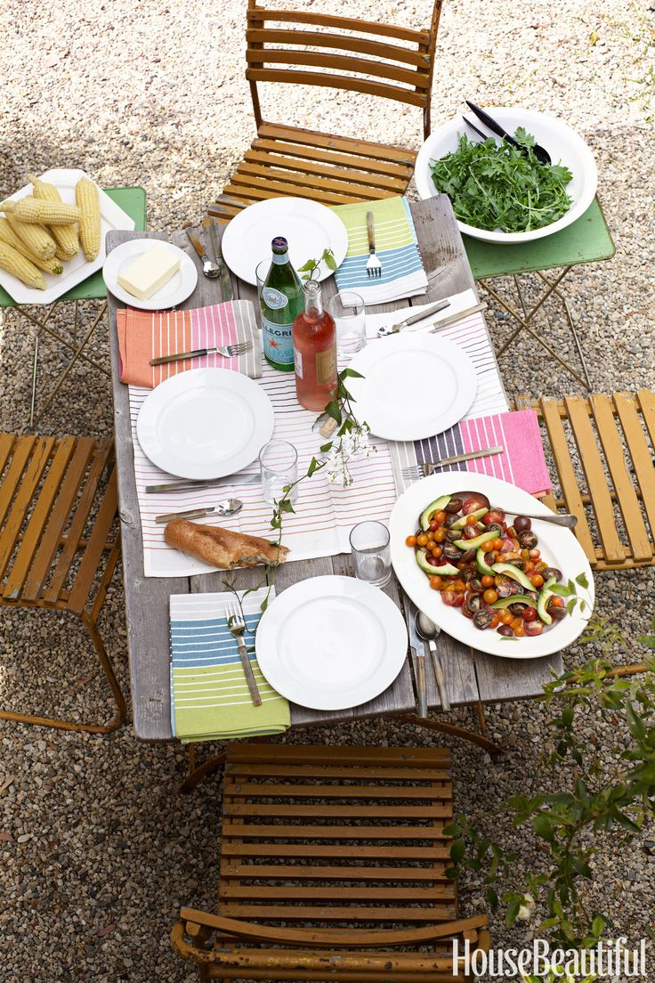 """A rustic French bistro table and chairs from Inner Gardens get vivid shots of color from linens Chris Barrett purchased in Milan. """"You feel as though you could be in Siena, except with a Weber barbecue,"""" she says.   - HouseBeautiful.com"""