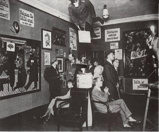Fotografía de la primera Feria Dadá Internacional en la galería de arte de Berlín del Doctor Burchard en 1922. Grosz es el segundo por la derecha y sentado a su lado se encuentra Heartfield.
