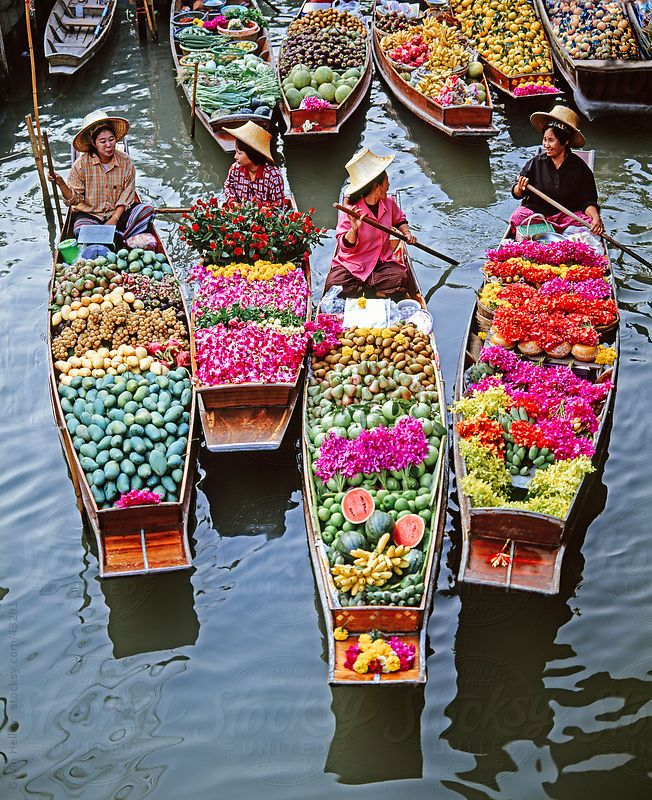 Market traders in boats laden with fruit and flowers, Bangkok, Thailand.