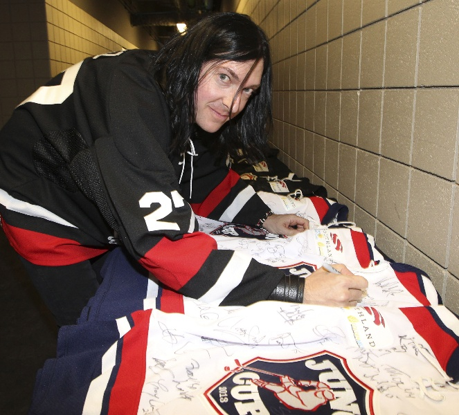 Musician Brent Fitz autographs hockey sweaters prior to the game.  CARAS/iPhoto