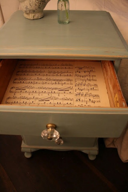 chalk paint, glass knobs, and vintage music sheets line the drawers