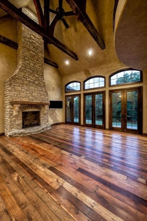 High ceilings with exposed beams, tall stone fireplace, and mixed tones hardwood floor.