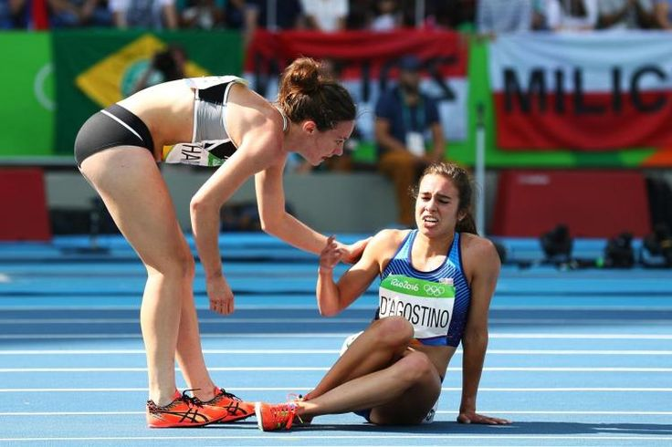 Abbey D'Agostino of the United States (r.) is assisted by Nikki Hamblin of New Zealand after a collision during a heat of the women's 5000-meter race.