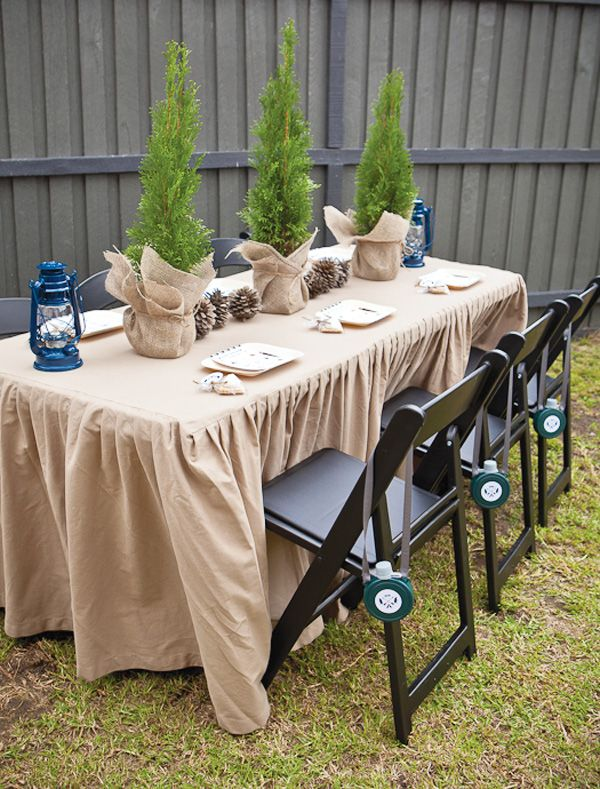 camping party: navy lanterns, burlap-tied trees, pinecones, personal plastic canteens tied on chairs