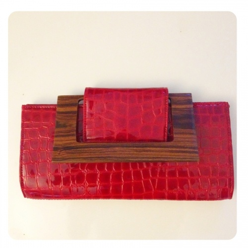 Ellie Clutch Patent Leather was $198 now $70.31.   A Classic rectangle clutch with a snapped flap closure. Add a hand-carved guyacan wood handle that can be used to carry or flipped down tho lie flat, and matte croc deerskin, and it becomes a totally exotic showpiece.