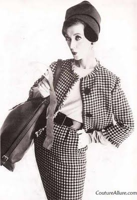 Jane Derby fashioned this suit of a houndstooth check in black, white and brown. The bodice of the dress is beige wool jersey. Love the fringed effect at the edges. Huge leather bag for travel by Mark Cross.