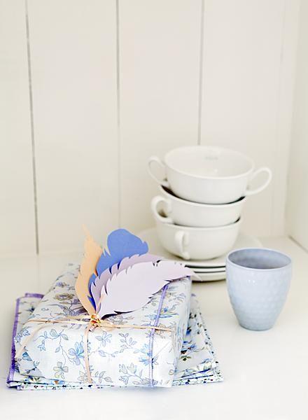 In plaats van cadeaupapier zijn hier leuke stoflapjes gebruikt. Na het uitpakken kunnen ze meteen dienstdoen als fleurig servet! Maak je pakje af met een corsage van veren, geknipt uit stevig papier en ietsje gevouwen in het midden.