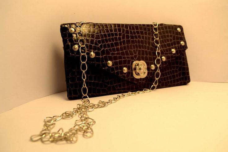Cartera- sobre de fiesta, realizado en cuero texturado color negro con cadena, tachas y broche torniquete en forma de flor.