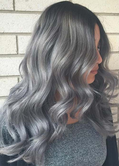 Dark Grey Hair Melting Into Light Silver Tips  Dark grey roots to light grey tips in shimmering soft waves look easy and ethereal. Her layers in the front are really showing up well with the color as well.