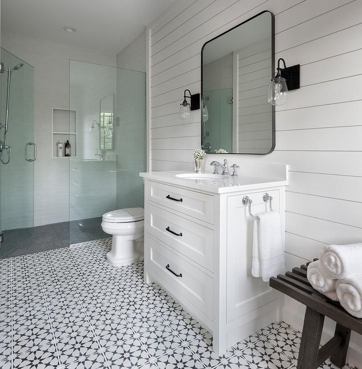Black and white mosaic floor tiles frame a white dresser-like washstand fitted with oil rubbed bronze pulls, a polished nickel towel bar, and a white quartz countertop finished with a round sink and a polished nickel faucet.