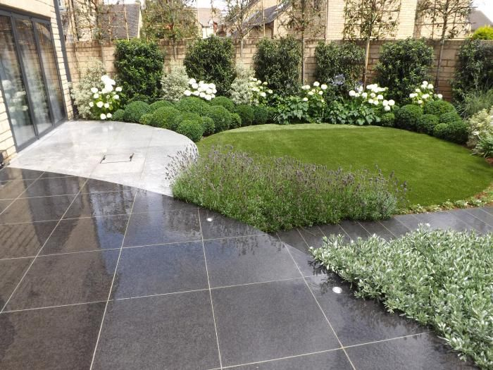 Hadingham Kirk Ltd used curved Black Pasalt paving slabs to create a unique circular garden design.