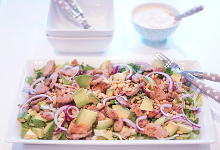 Avocado salad with pork: (For 2): - 500 g pork filet - salt and pepper - butter for frying - 1 package rocket - 1/2 head iceberg lettuce - 2 avocados - 1 red onion - 2 dl toasted pine nuts - juice of half a lemon. Sour cream dressing: - 3 dl sour cream - chili sauce - onion powder - paprika powder - erythritol - chili powder